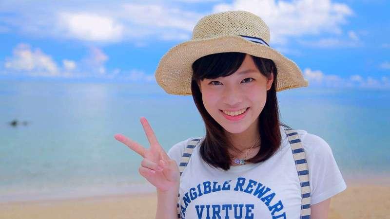麻宮まどかがビーチをバックにムギワラ帽子をかぶり笑顔